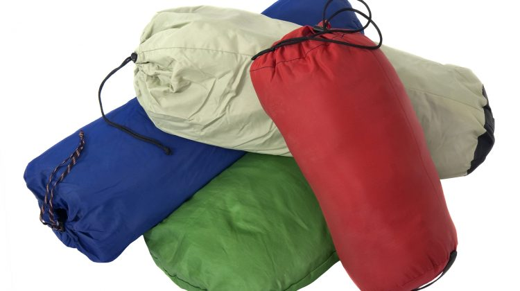 a pile of colorful bags with camping equipment (tent sleeping bag pad) isolated on white